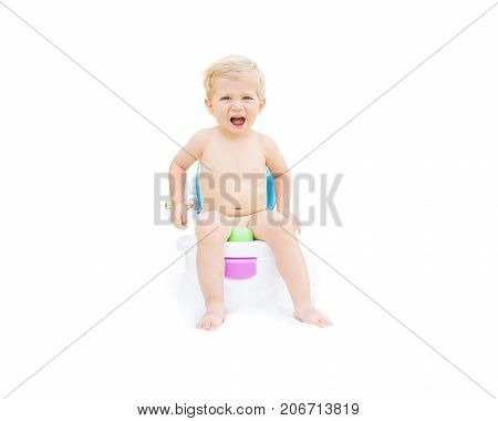 Infant boy white caucasian smiling and sitting on the potty with white background.