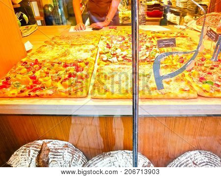 Venice, Italy - May 04, 2017: People cooking pizza on May 04 2017 in Venice, Italy. There is a bill before the Italian Parliament to safeguard the traditional Italian pizza by specifying ingredients and methods.