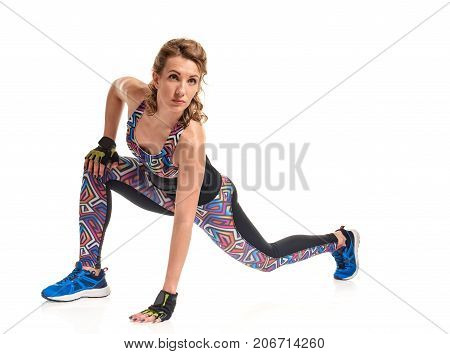 Young sportwoman making stretching exercises on white background
