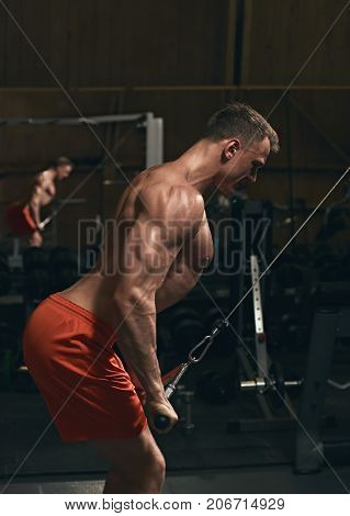 Muscular sporty man exercising with stretching band in the gym