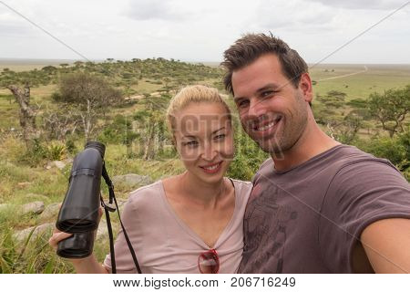 Casual adult couple taking selfie on african wildlife safari in Serengeti national park, Tanzania, Africa.