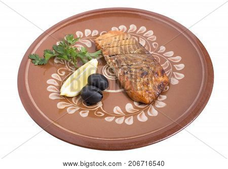 Salmon steak on a clay plate with lemon, parsley and olives. Isolated on a white background.