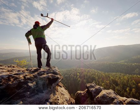 Tourist With Medicine Crutch Above Head Achieve Mountain Peak. Hurt Backpacker With Broken Leg