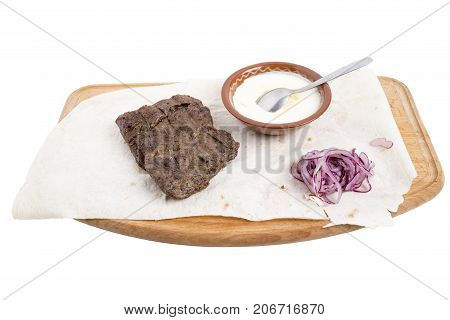 Delicious beef steak with sauce and red onion on a wooden board. Isolated on a white background.
