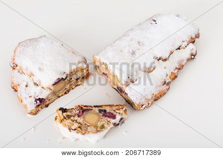 Delicious pie with dried fruits and powdered sugar.  Isolated on a white background.