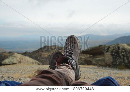 Legs of a man resting in boots for mountain tracking against the backdrop of mountains and valleys with noisy clouds Hiking boots in the mountains. Resting time. Freedom concept