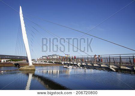 Swansea Marina, UK: June 29, 2017: The Millennium footbridge over the River Tawe at Swansea Marina in the popular SA1 Maritime Quarter. Sailboats are moored in the marina.