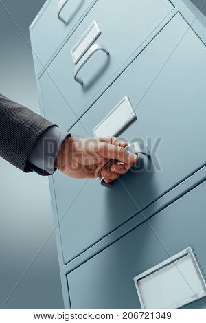 Office Clerk Searching Files In The Filing Cabinet