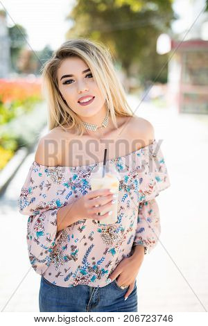 Beautiful And Young Smiling Girl Drinking Lemonade And Keeping Phone In Hand While Walking Through C