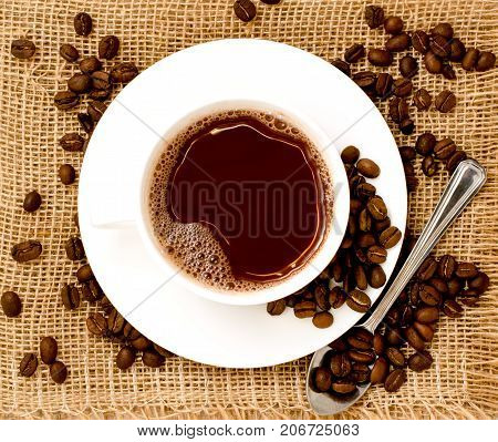 Cup Of Coffee And Coffee Beans On Sackcloth.