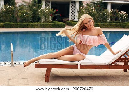 Girl With Blond Hair In Swimming Suit, Relaxing Near Swimming Pool