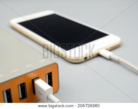 Close-up image of smart phone charging with multiport USB power adaptor on gray background Selective focus