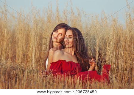 Young women in dry grass in the field they are happy and smiling.