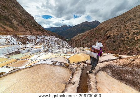Worker Carrying A Big Sack Of Salt, On The Terraced Salt Pans In Maras, Urubamba Valley, Peru. Manua