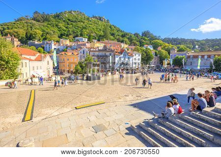 Sintra, Portugal - August 8, 2017: Tourists sitting on steps of National Palace of Sintra in the popular main Amelia Square with Castle of the Moors on background. Sintra urban center in a sunny day.