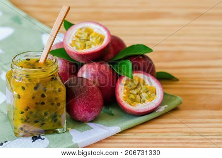 Homemade passion fruit jam in bottle put on wood table. Passion fruit jam background with copy space for your design. Fresh passion fruit and homemade jam on wood table in natural tone style concept. Passion fruit jam ready to served.