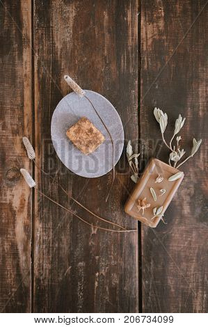 Top view of still life with handmade organic rustic soap with dried flowers marble or stone soap-dish on dark wooden table background. Vertical shot.