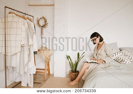 Young pretty lady with short black hair sits on bed in morning in her big white room and reads book in glasses and linen beige robe. Space for your text.