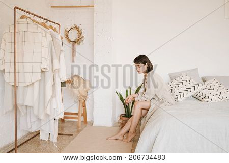 Young sexy lady with short black hair in linen beige robe sits on bed in morning in her big white room looks down and thinks what to wear today. Space for your text.