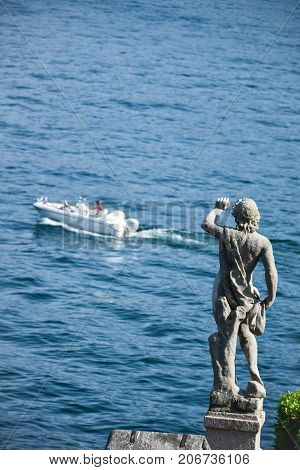 Statue in the gardens of Isola Bella gazing at the lake waving at a boat sailing on the blue rippled surface of the Lago Maggiore lake Italy