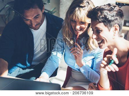Group of coworkers making great conversation during work process in modern office.Business people meeting concept.Blurred background.Horizontal