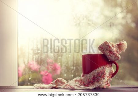 hot red mug in scarf and hat on the background window after the rain / time to chill out