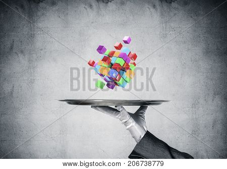 Cropped image of waiter's hand in white glove presenting multiple cubes on metal tray with gray concrete wall on background. 3D rendering.