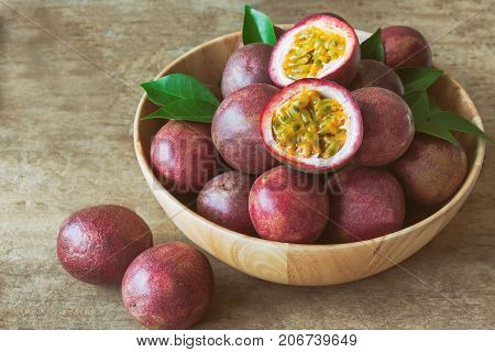 Passion fruit on wood bowl put on wood table in vintage tone style for background or wallpaper. Ripe passion fruit so sweet and sour suitable make dessert for summer. Passion fruit is tropical fruit. Prepare fresh passion fruit for cooking.