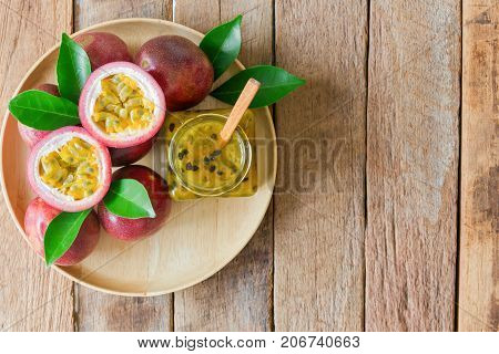 Homemade passion fruit jam in bottle on wood plate. Passion fruit jam on wood table in top view flat lay style with copy space. Fresh passion fruit and homemade jam on wood table natural concept. Delicious passion fruit jam ready to served.