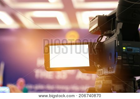 Blur of Video camera or camcorder operator working for record couple speaker or Presenterson stage in conference and convention hall in Vietnam blak white screen on recording