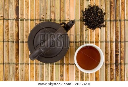 Oriental Clay Teapot With Cup Of Brewed Tea & Loose Tea Leaves