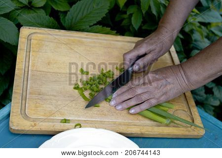 Female hands chopping onion on a top of the blue table outdoor photo