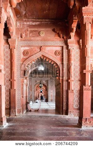 Fatehpur Sikri, India - 13th Aug 2017: Beautiful red sandstone hallway with people sitting outside the Salim Chishti Mosque. The arched gates and beautifully engraved stone makes this a very relaxing place