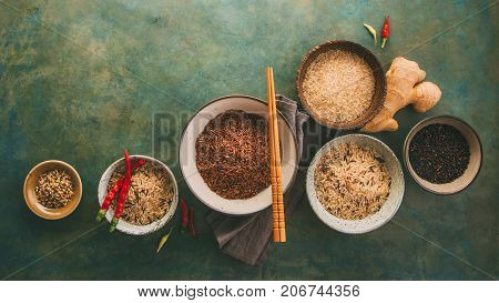 Assortment of different rice in bowls and spices: white rice red rice black rice a mixture of wild and brown rice. Healthy food background wiht copy space.