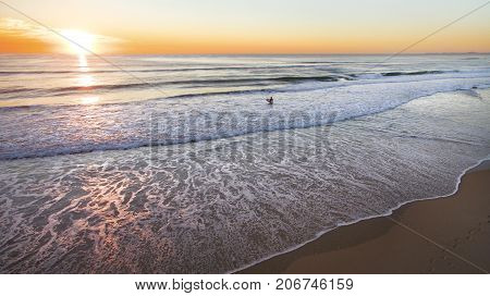 Beach aerial overlooking a surfer wading into the ocean with a colorful sunrise over the ocean.