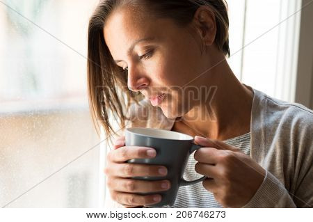 Woman Holding A Cup Of Coffee Portrait Next To A Window