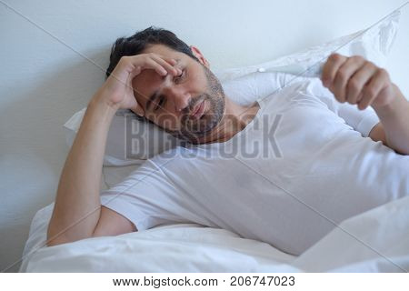 Sick Man In Bed Measuring Temperature And Looking Thermometer