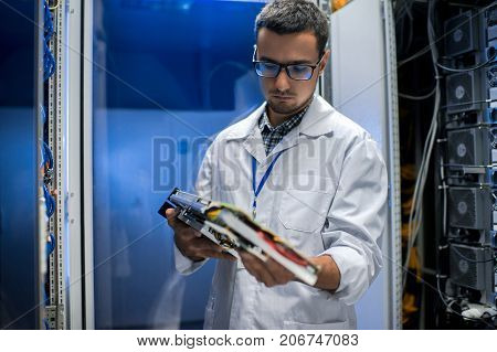 Portrait of young man wearing lab coat and glasses holding blade server while working with supercomputer