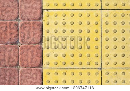 Tactile Paving Slabs on the Sidewalk of Square Red Paving Stones. Braille Block Tactile Paving for Blind Handicap