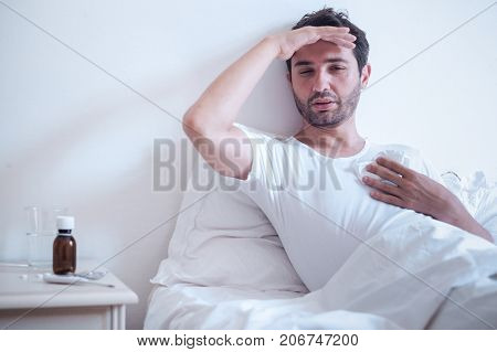 Sick Man In Bed Measuring Temperature And Feeling Bad