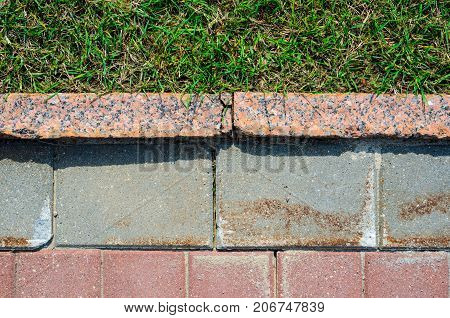 Old red and gray granite pavement and grass in garden decorative texture line dividing nature and civilization concept.