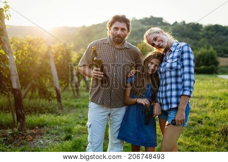 Wine grower family tasting wine in winery vineyard