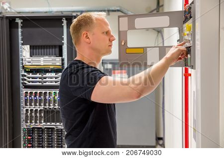Side view of confident male technician checking fire panel in datacenter