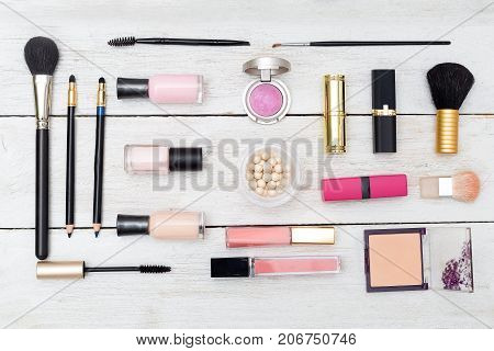 A variety of women's cosmetics lies on a wooden background. View from above