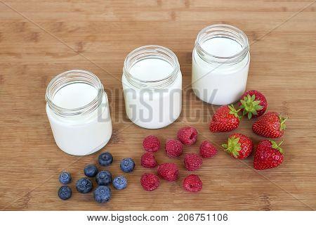 Three glass jars with yogurt and variation of berries - diagonally