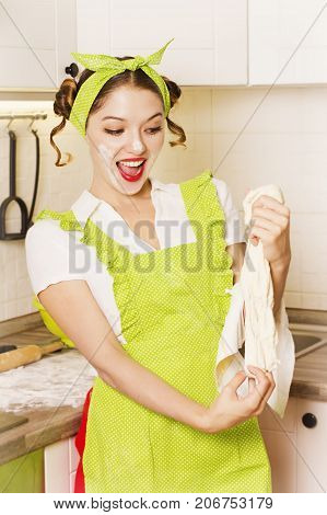 Pretty housewife in green apron cooking in the kitchen