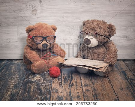 Two toy bears reading and crochet. As an old grandma and grandpa. The concept of old age family old couple together