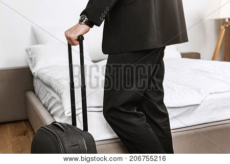Close up detail of businessman in black suit holding suitcase in hands going to leave hotel room and fly home by plane from business trip