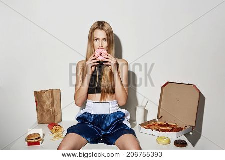 Joyful beautiful female model with blonde hair in sport wear sitting on table, eating junk food, looking in camera with cute donut in mouth.