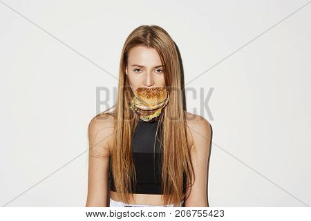 Attractive young girl with light long hair in black sport top holding burger in mouth, looking in camera with serious and flirty expression